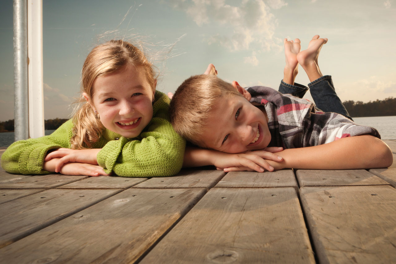 Children smiling on a pier